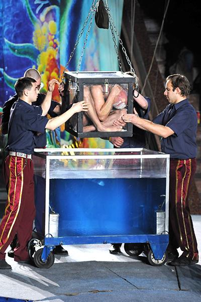 Человека-амфибию (Ахмет Сурхатилов) закрытого в стеклянном ящике погружают в аквариум сводой на 5 минут в Киевском цирке 27 января 2011 года. Фото: Владимир Бородин/The Epoch Times Украина