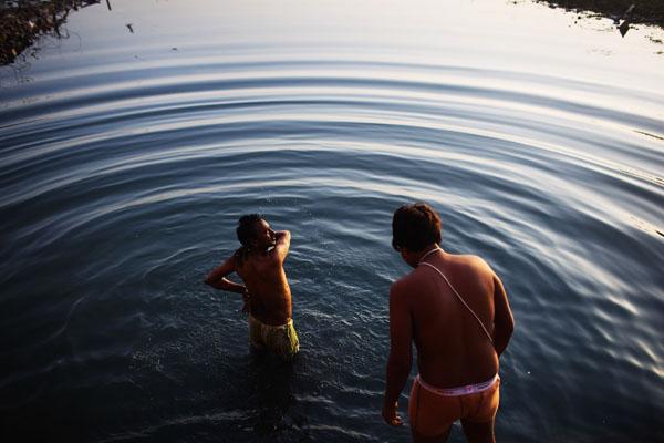 Мужчины моются на берегу реки Ямуна. Четверть населения Дели лишена воды в своих домах, подаваемой по трубопроводам. Индия. Фото: Daniel Berehulak/Getty Images