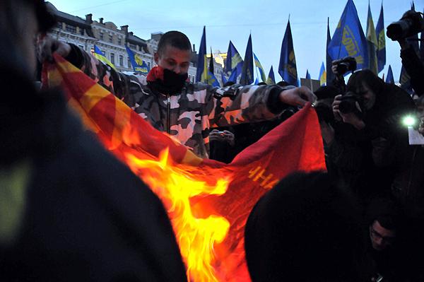 Человек в маске сжигает флаг с коммунистической символикой во время марша за признание УПА в Киеве 14 октября 2010 года. Фото: Владимир Бородин/The Epoch Times
