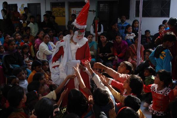Рождественские праздники у школьников. Санта дарит ученикам конфеты. Фото: DIPTENDU DUTTA/AFP/Getty Images