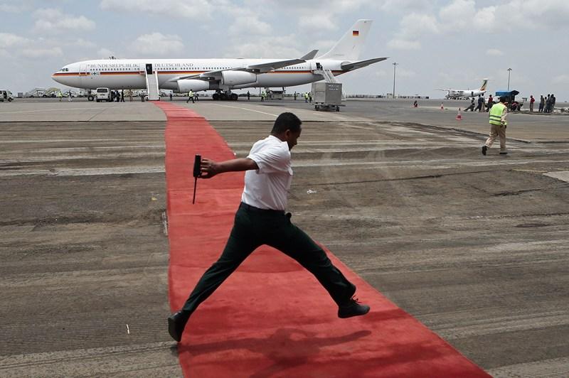 Аддис-Абеба, Эфиопия, 20 марта. Техник аэропорта перепрыгивает через красную дорожку перед отлётом президента Германии Йоахима Гаука, посетившего страну с 4-дневным визитом. Фото: Sean Gallup/Getty Images