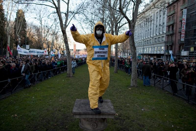 Мадрид, Испания, 23 февраля. Надпись на костюме демонстранта: «Ваша демокретиния смердит». Жители протестуют против мер жёсткой экономии в связи с кризисом в стране. Фото: Pablo Blazquez Dominguez/Getty Images