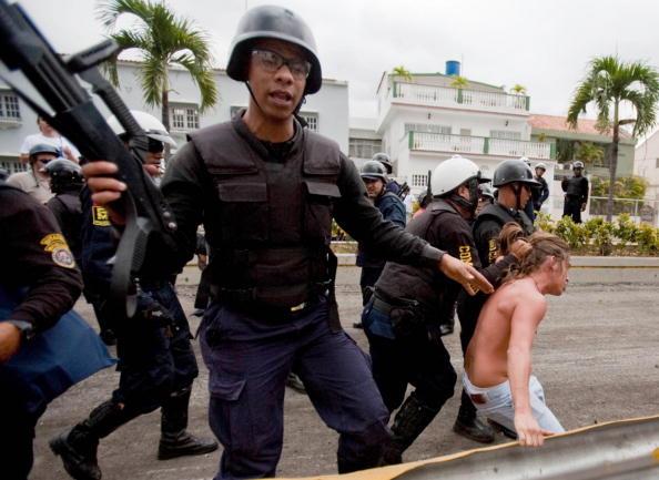 Полиция арестовывает студента, участвующего в акции протеста против запрета вещания канала RCTV, критикующего правительство. Каракас, Венесуэла. Фото: MIGUEL GUTIERREZ/AFP/Getty Images