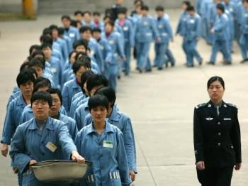 Заключённые под полицейским эскортом во время дня открытых дверей в тюрьме в Нанкине в 2005 году. Фото: STR/AFP/Getty Images