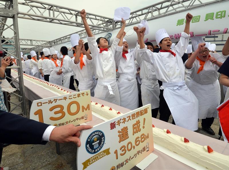 Токио, Япония, 17 апреля. Ученики кондитерского колледжа изготовили самый длинный в мире рулет (130,68 м). На его изготовление ушло 54 кг муки, 43 кг сахара и 2682 яйца. Длина прежнего рекордсмена — 115,09 м. Фото: YOSHIKAZU TSUNO/AFP/Getty Images