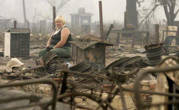 Женщина сидит в окружении остатков своего сгоревшего дома в селе Моховое, около 130 км от Москвы 31 июля 2010 года. Фото: ARTYOM KOROTAYEV/AFP/Getty Images
