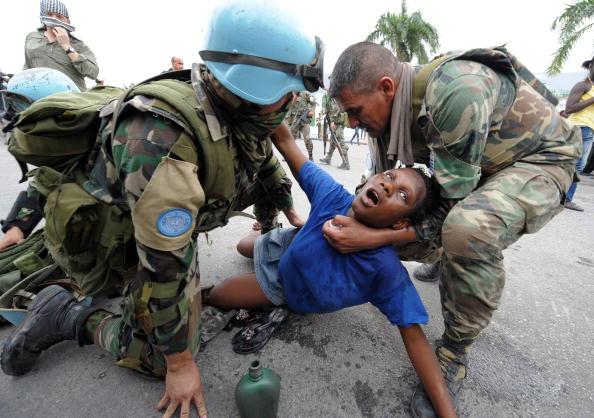 Беременной женщине помогают солдаты ООН, поскольку пункт распределения помощи возле президентского дворца охвачен хаосом. Порт-о-Пренс, Гаити. 25 января 2010. Фото: Джевела Самада/AFP/Getty Images