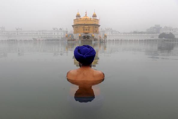 Индийский сикх принимает священное омовение в Сарове - водохранилище возле Золотого храма в Амритсаре. 20 января 2010. Фото: Нариндер НАНУ / AFP / Getty Images