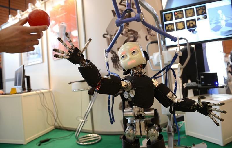 Лион, Франция, 19 марта. Гуманоидный робот ICub пытается взять мяч на европейском саммите робототехники «Innorobo 2013». Фото: PHILIPPE DESMAZES/AFP/Getty Images
