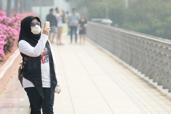 Девушка в марлевоъ повязке фотографирует местные виды в Сингапуре. Город окутал смог. Фото: ROSLAN RAHMAN/AFP/Getty Images