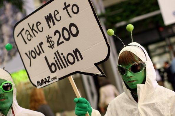 Активист, одетый как инопланетянин, держит в руках плакат, на котором написано «Включи меня в свой 200-й миллиардный проект» во время второго дня саммита ООН по проблеме изменения климата. Копенгаген, Дания. Фото: Miguel Villagran/Getty Images