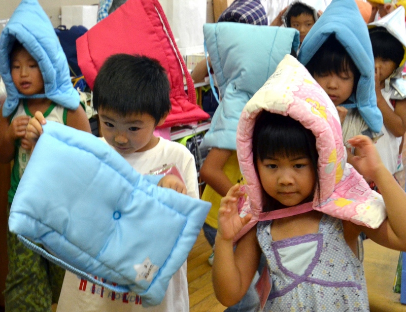 Токио, Япония, 3 сентября. Ученики начальной школы в защитных накидках. В стране прошли общенациональные учения по защите от последствий землетрясений. Фото: YOSHIKAZU TSUNO/AFP/GettyImages