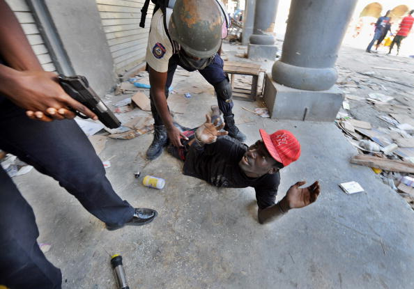 Гаитянские полицейские избивают грабителя в Порт-о-Пренсе. Признаки нормальной жизни начали возвращаться в некоторые районы Порт-о-Пренса,но грабежи все еще продолжаются. Фото: Джевел САМАД /AFP/Getty Images