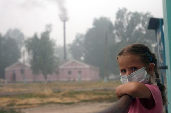 Девочка в маске смотрит с балкона в селе Белоомут, находящемся в 130 км от Москвы. Фото: ANDREY SMIRNOV/AFP/Getty Images