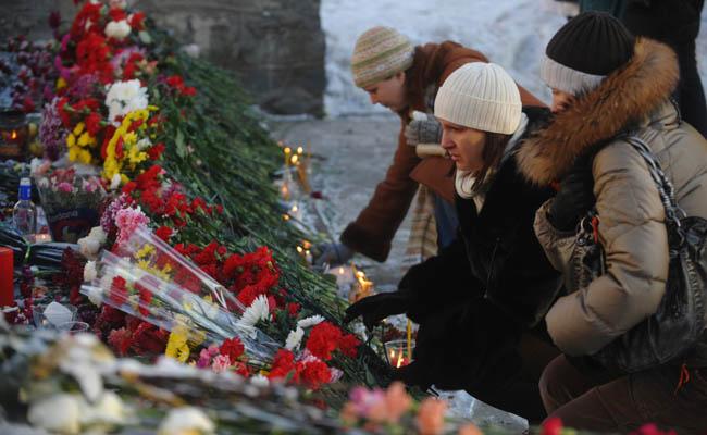 Женщины кладут цветы напротив ночного клуба «Хромая лошадь» в Перми. Как минимум 109 человек погибли в результате взрыва пиротехники и последовавшего за ним пожара в ночном клубе. Пермь, Россия. Фото: DMITRY KOSTYUKOV/AFP/Getty Images