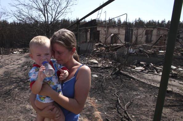 Женщина с ребенком уходит от своего сгоревшего дома на окраине Воронежа 31 июля 2010 года. Фото: Alexey SAZONOV/AFP/Getty Images