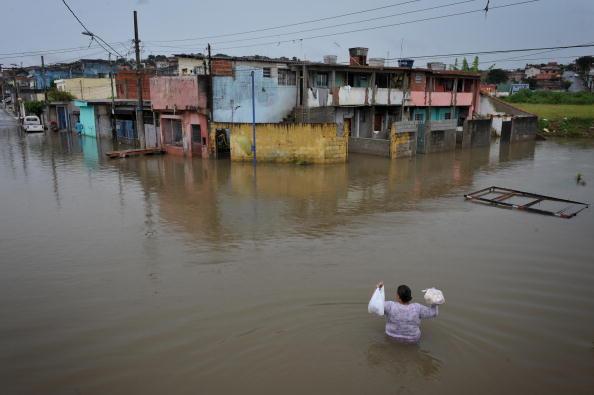 Местный житель пробирается домой с хлебом и молоком через затопленную улицу. Продолжительные двухмесячные дожди в Бразилии затопили северный и восточный районы Гуарульюса. Погибло 69 человек.. 29 января 2010. PHOTO/Mauricio LIMA /AFP/Getty Images