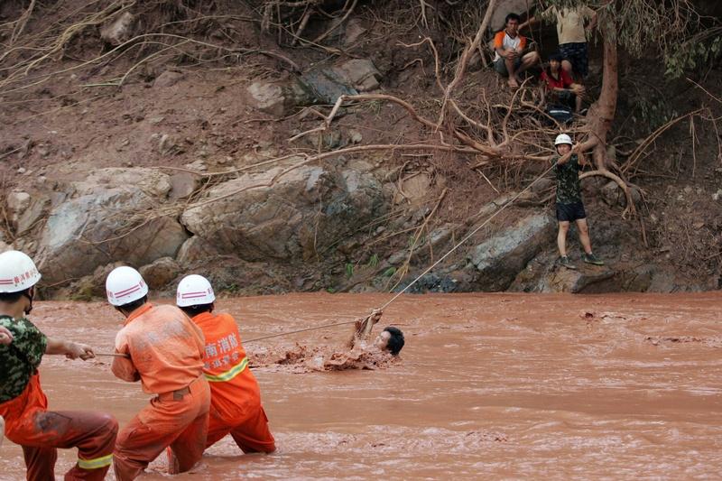 Цзингу, провинция Юньнань, Китай, 31 июля. Спасатели помогают жителю переправиться через реку, перекрытую грязевым оползнем. Фото: STR/AFP/GettyImages