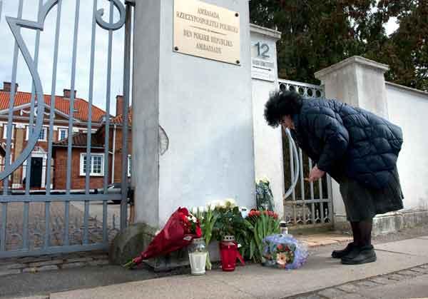 Женщина кладет цветы около ворот польского посольства в Копенгагене. Фото: KELD NAVNTOFT/AFP/Getty Images