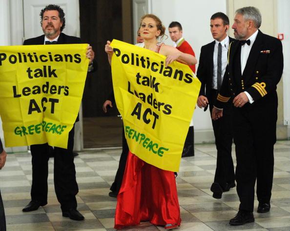 На торжественном ужине, который давала королева Дании Маргрете II в честь глав государств и правительств, активисты Гринпис развернули плакаты с надписью: 'Политики говорят - лидеры действуют'.Фото: ERIC FEFERBERG/AFP/Getty Images