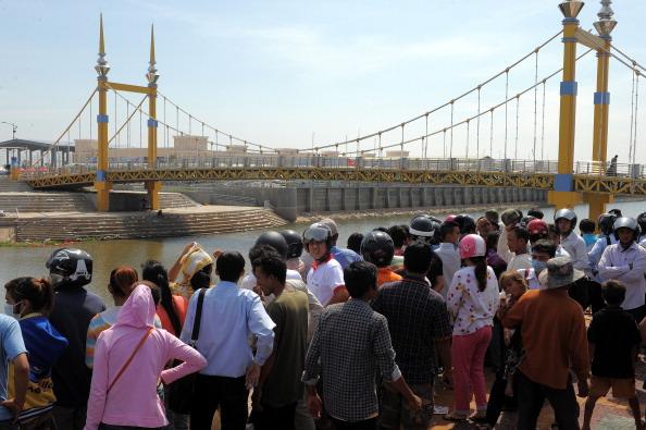 Жители Камбоджи смотрят на оставшийся мусор на мосту, где недавно произошла давка во время фестиваля в Пномпене, 24 ноября 2010 года. Сотни скорбящих камбоджийских семей вышли 24-25 ноября на траурную церемонию по погибшим родным, а также выразить свой гн