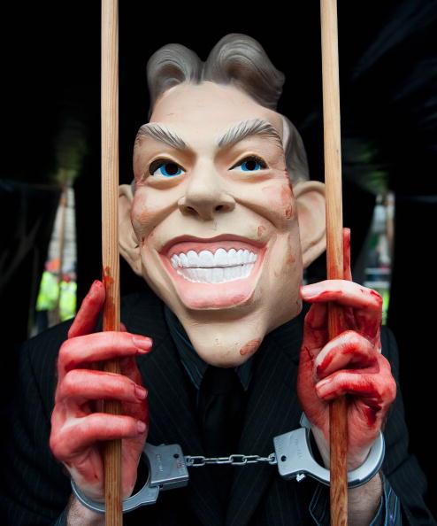 Протестующий, одетый в маску Тони Блэра участвует в акции протеста возле конференц -центра королевы Елизаветы. Бывший премьер-министр Великобритании (с мая 1997 по июнь 2007 года), был призван к ответу председателем комиссии сэром Джоном Чилкотом по пово
