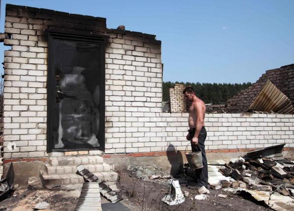 Мужчина смотрит на остатки своего сгоревшего дома в Воронеже 2 августа 2010 года. Фото: Alexey SAZONOV/AFP/Getty Images