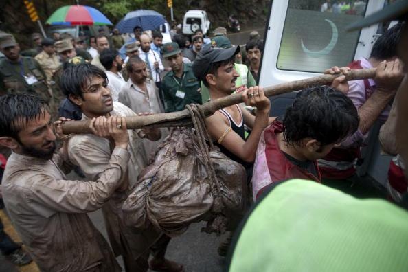 Пакистанские работники гуманитарных организаций выносят останки жертв с места крушения самолета в Пакистане. Фото: BEHROUZ MEHRI/AFP/Getty Images