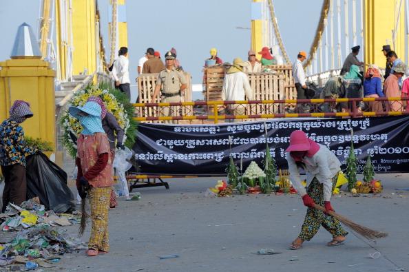 Камбоджийские рабочие убирают мусор на месте давки на мосту, Пномпень, 24 ноября 2010 года. Сотни скорбящих камбоджийских семей вышли 24-25 ноября на траурную церемонию по погибшим родным, а также выразить свой гнев по поводу неорганизованной безопасности