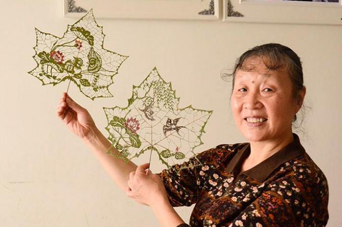 Ду Ваньли со своими работами, сделанными из кленовых листьев. Фото: People's Daily