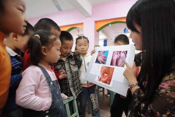 У м. Хефей провінції Аньхой співробітник Центру контролю та профілактики захворювань розповідає дітям про те, як уникнути зараження хворобою HFMD. Фото з aboluowang.com