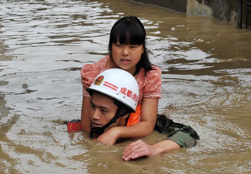 Провінція Сичуань, Китай, 11 липня. Рятувальник евакуює жінку із затопленої місцевості. Зливові дощі викликали місцями розлив річки Туо. Фото: AFP/AFP/Getty Images