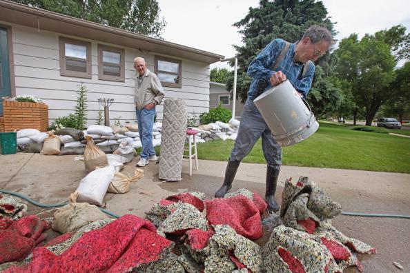 Жители г. Майнот убирают мусор после ухода наводнения. Северная Дакота, США. Фото: Scott Olson/Getty Images