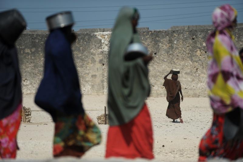 Сомалийская девочка несет над головой горшок, наполненный горячей пищей , в то время, как другие ждут в очереди, чтобы получить свой рацион питания на точки распространения в столице Могадишо в Сомали 18 августа 2011 года. Около 12 миллионов человек в