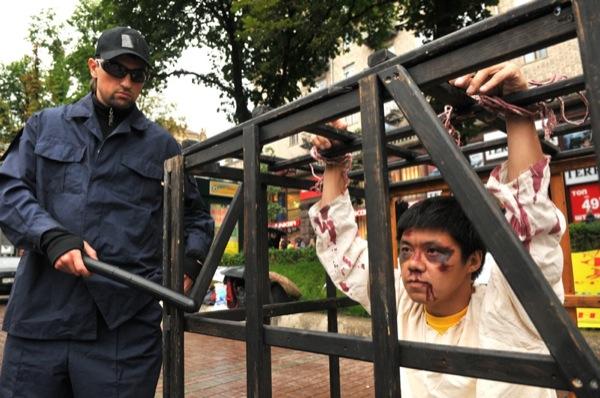 Ли на мирной акции протеста против пыток в Китае. Инсценировка метода пытки заключение в клетке, которая используется в тюрьмах Китая в ходе преследования Фалуньгун. Инсценировка проводится с целью: привлечь общественное внимание к нарушению прав челове