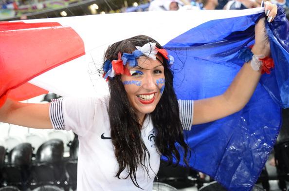 Вболівальниця національної збірної Франції намагається захиститися від дощу, на матчі Україна — Франція, який на деякий час був припинений через негоду 15 червня 2012, на Донбасс Арені в Донецьку. Фото: Франк Фіфе/AFP/Getty Images