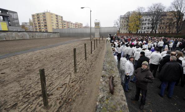 Люди вставляют розы в щели стоящей стены на памятной церемонии на ул. Бернауэр-штрассе. Фото: Getty Images