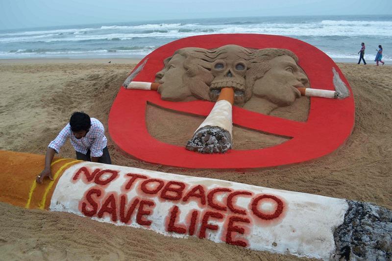 Пури, Индия, 30 мая. Художник завершает изготовление скульптуры из песка «Нет табаку, сохраним жизнь», созданной к празднованию Всемирного дня отказа от курения. Фото: ASIT KUMAR/AFP/Getty Images