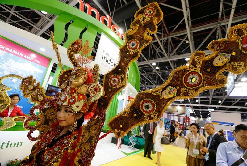 Дубай, Об'єднані Арабські Емірати, 6 травня. Індонезійка в національному костюмі зустрічає відвідувачів на арабській міжнародній туристичній виставці. Фото: KARIM SAHIB/AFP/Getty Images