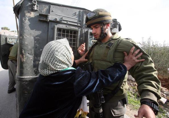 Палестинка умоляет израильского солдата отпустить мирного активиста, которого арестовали во время акции протеста против израильского разделительного барьера на Западном береге реки Иордан. Фото: MUSA AL-SHAER/AFP/Getty Images