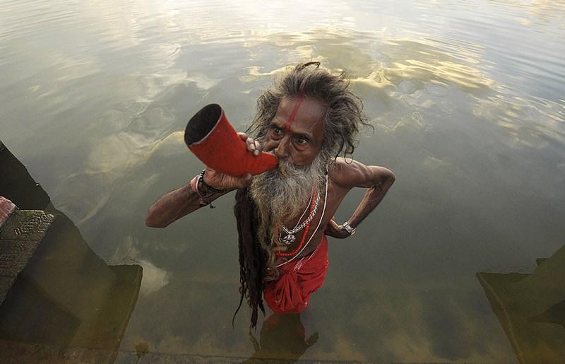Агартала, Индия, 15 июля. Садху (индийский святой) трубит в рог на фестивале Кхарчи Пуджа, во время которого индийцы показывают уважение земле, питающей своими ресурсами человечество. Фото: ARINDAM DEY/AFP/Getty Images