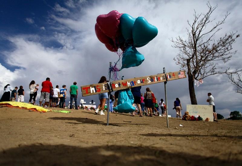 Аврора, штат Колорадо, США, 24 июля. Надувные шары в форме сердец — в память о погибших на премьере фильма «Возвращение тёмного рыцаря». Надпись на доске: «Наши солдаты гибнут не ради этого». Фото: Joshua Lott/Getty Images