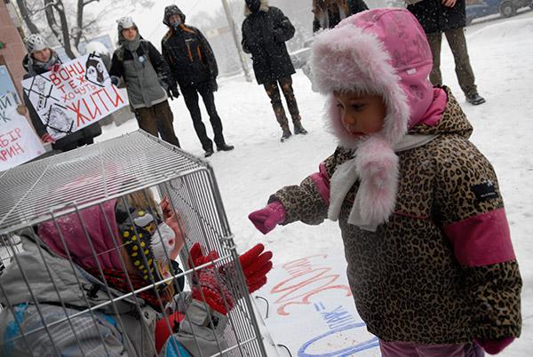 Девочка подошла к клетке вовремя акции «Киевский зоопарк – концлагерь для животных», которая прошла возле зоопарка в Киеве 20 декабря. Фото: Владимир Бородин/The Epoch Times