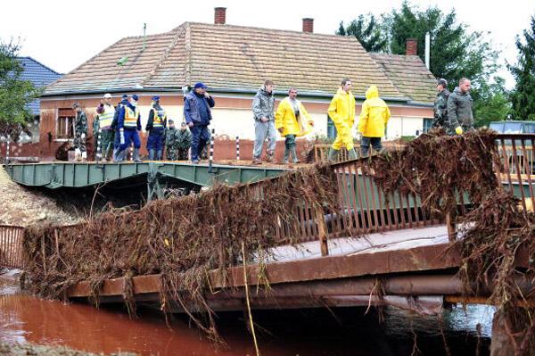 Местные жители и спасатели ходят по временному мосту в Kolontar около 160 км к северо-западу от столицы Венгрии Будапешта. Фото: ATTILA Kisbenedek/afp/getty Images