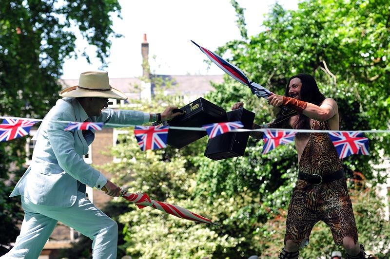 Лондон, Англия, 13 июля. Участники эксцентричной олимпиады среди джентльменов соревнуются в битве на зонтиках. Фото: CARL COURT/AFP/Getty Images
