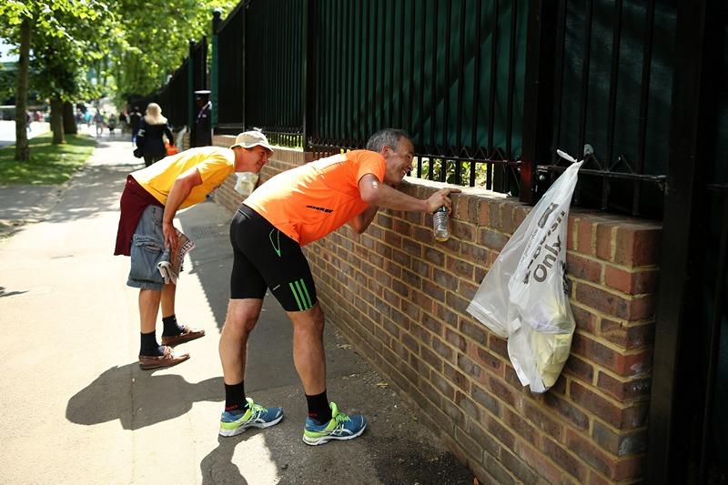 Лондон, Англия, 25 июня. Фанаты подсматривают за тренировкой спортсменов на корте клуба крокета и тенниса, участвующих в Уимблдонском турнире. Фото: Dan Kitwood/Getty Images
