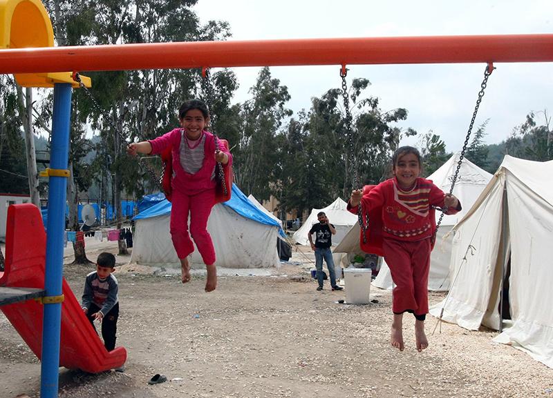 Сирийские дети-беженцы играют на качели в лагере беженцев в Yayladagi 26 марта 2012 года. Фото: ADEM ALTAN/AFP/Getty Images