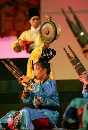 Женщина, играющая на традиционном духовом инструменте. Пекин, 4 июня 2005 г. Фото: AFP/Getty Images