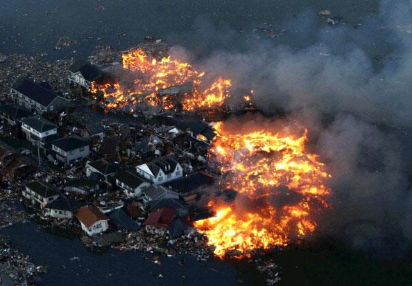 Горящие дома после удара цунами в городе Натори в префектуре Мияги, после сильного землетрясения в Японии 11 марта 2011 года. Фото: AFP PHOTO / YOMIURI SHIMBUN