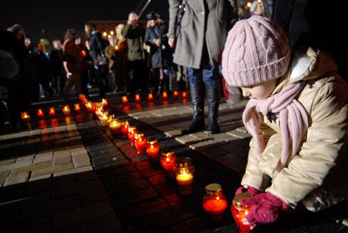 Ребенок ставит свечку в память о невинных жертвах Голодомора. Фото: Владимир Бородин/ Великая Эпоха